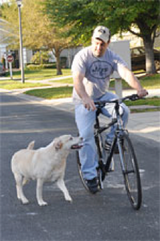 Seth Reichelson riding a bike with his dog Noodles